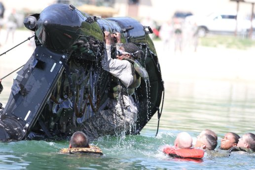 Cpl. Denise Houston, a Ridgeland, S.C., native, hangs on to a Zodiac boat as she, along with fellow Soldiers, try to get the watercraft turned back over Aug. 14 at Fort Leonard Wood's Training Area 250 Lake. Troops from the Forward Support Company, 94th Engineer Battalion, part of the 4th Maneuver Enhancement Brigade, 1st Infantry Division, were challenged with various tasks, including boat drills and swimming with waterproofed gear.